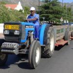 A worker drives a tractor down the main road of Franschhoek.