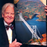 Augusts Upitis displays an award winning print of Bear Mountain Bridge on the Hudson River. After earning his Master Photographer Certification he continued entering and winning many contests.