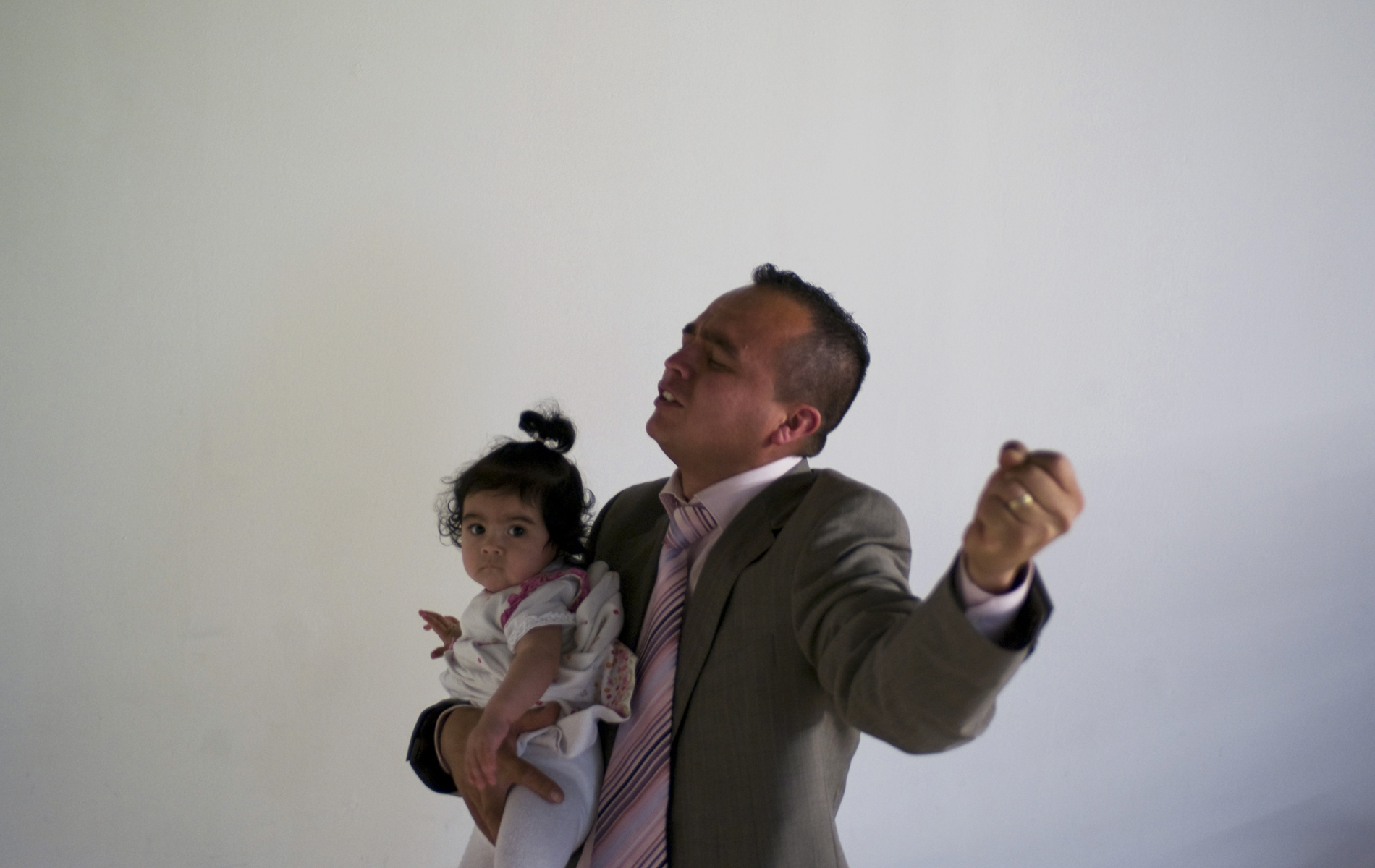 A father prays while holding his daughter during a Pentecostal service in Tarragona, Spain. © Damaso Reyes