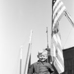 Alvis Upitis photographed by father Augusts Upitis on arrival in NY Harbor in June, 1950.  My father was a patriot from day one and photographed flags any time he could.