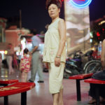 An old Chinese woman on the street at night © Justin Guariglia