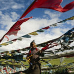 A Tibetan pilgrim hoists prayer flags over a mountain pass in Tibet. © Justin Guariglia