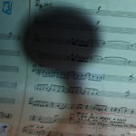 The shadow of a trumpet falls on sheet music during a performance.