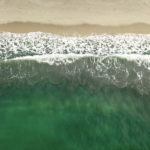 An aerial view of waves crashing down on a pristine beach © Justin Guariglia