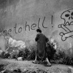Sarajevo - A City Under Siege © Tom Stoddart/Getty Images | Welcome to hell - a woman hurries past graffiti in the area known as 'Sniper Alley' in Sarajevo's main thoroughfare, during the siege in 1992.