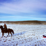 A cattle rancher tows his children on their sled with his horse. © Todd Korol