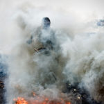 A Man standing in a cloud of smoke as he burns a copper cable
