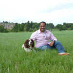 The author in front of The Carnegie Club at Skibo Castle in Dornoch, Scotland with resident pooch AC. By Varun Sharma
